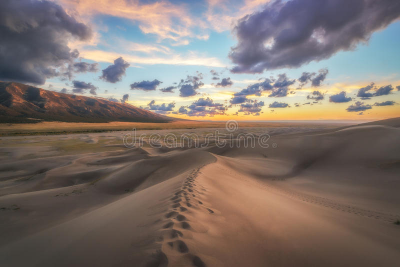 Foot prints on a sand dune at sunset. stock photo