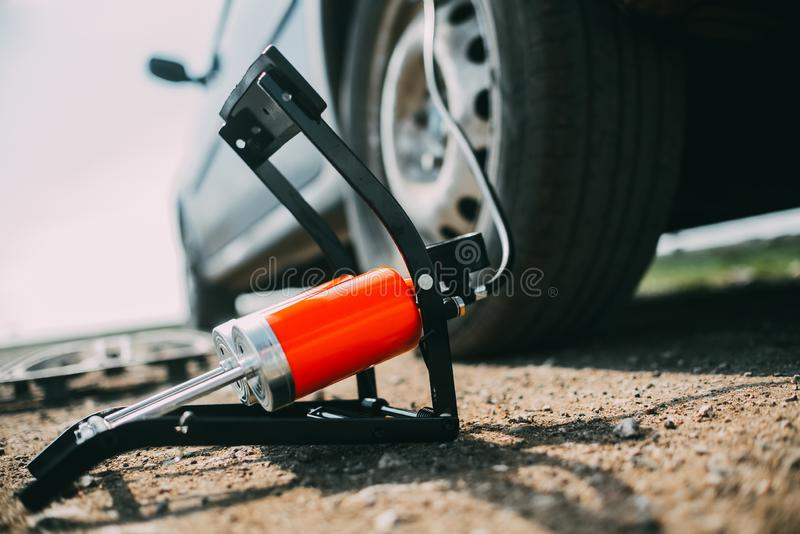 Foot pump on the floor next to the car and wheel royalty free stock image