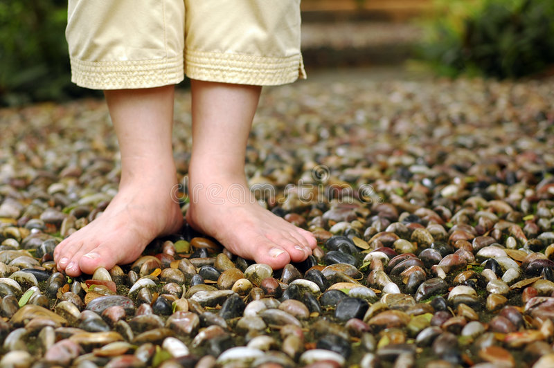 Foot reflexology. A closeup on foot reflexology walk path at garden. Shallow focus on foot and stone royalty free stock photography