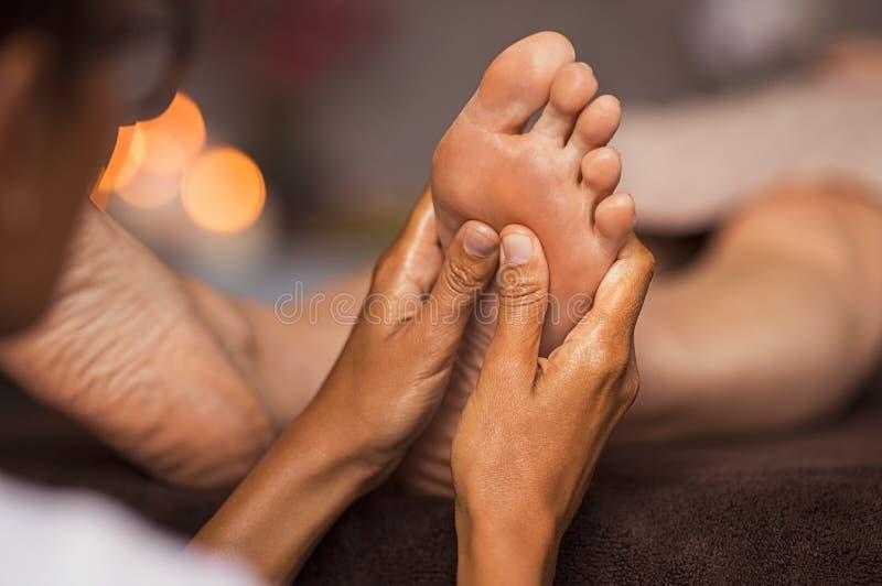 Foot reflexology massage. Closeup of masseuse doing foot reflexology to women at spa. Therapist hands doing foot massage at wellness center. Woman receiving a