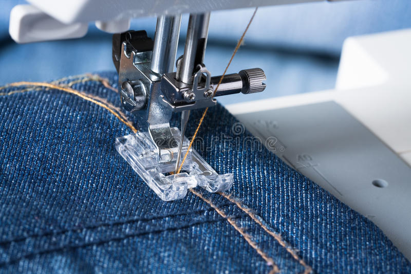 Foot Of Sewing Machine On Jeans Fabric. Jeans. Foot Of Sewing Machine On Jeans Fabric stock photos