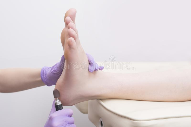 Foot skin treatment process. Gloved hands with a pedicure machine. Close-up.  stock photos