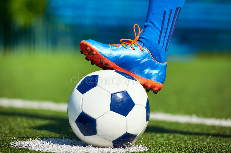 Foot of soccer player in football boot on ball stock images