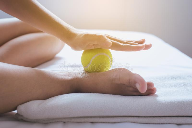 Foot soles massage,Woman hand giving massage with tennis ball to her foots in bedroom stock image