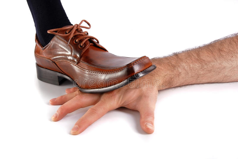 Foot stepping on a hand stock photography