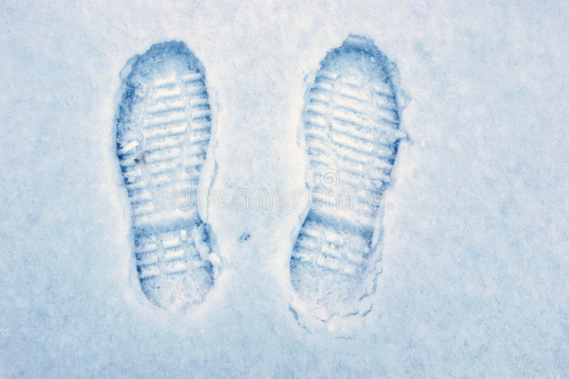 Foot steps on snow ground royalty free stock photo