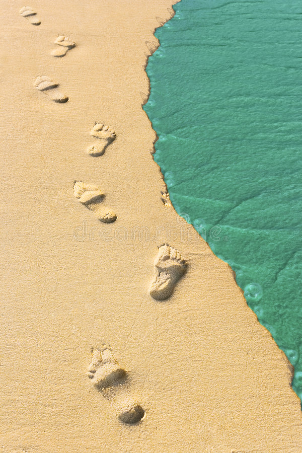 Foot steps and surf on tropical beach stock photos