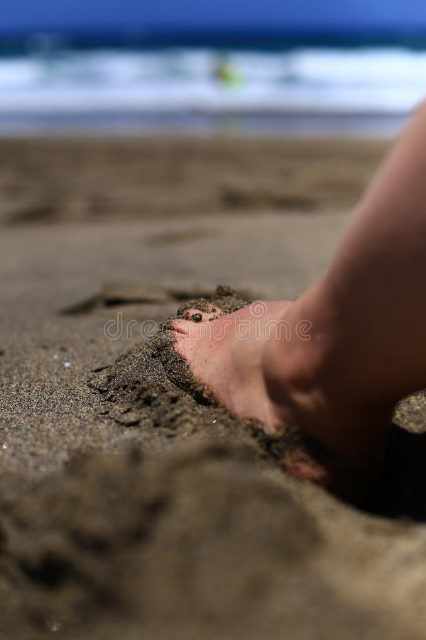 Foot submerged in the sand on the beach against the waves of the ocean. (fuertaventura royalty free stock photography