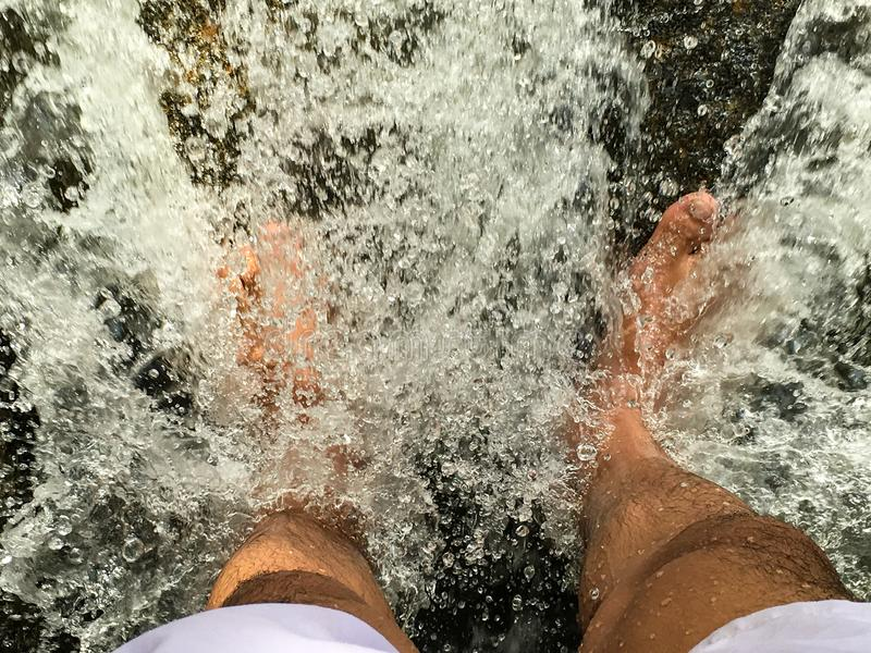 Image of the two feet blocking the waterfall. The foot of the two feet that lie in the flowing waterfall Until the water splits into the pellets royalty free stock photography