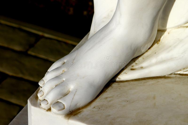 Foot of white beautiful female marble statue close up. On dark background stock photo