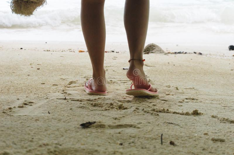 Foot of woman wearing pink sandal standing on sand beach are background. this image for nature and body part concept. Foot of young woman wearing pink sandal stock photography
