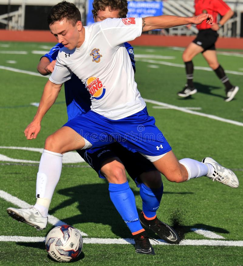 Football action for the loose ball. Football players get tangle while trying to retrieve the ball at the professional Soccer event, pro football game, NPSL stock photo