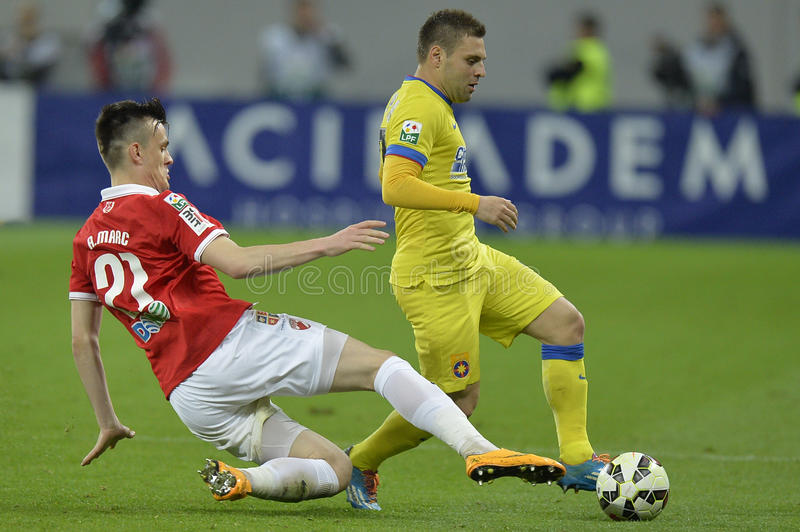 Football action - sliding tackle. Andrei Marc player of Dinamo Bucharest takles Adrian Popa of Steaua Bucharest during the Romanian football derby stock photography