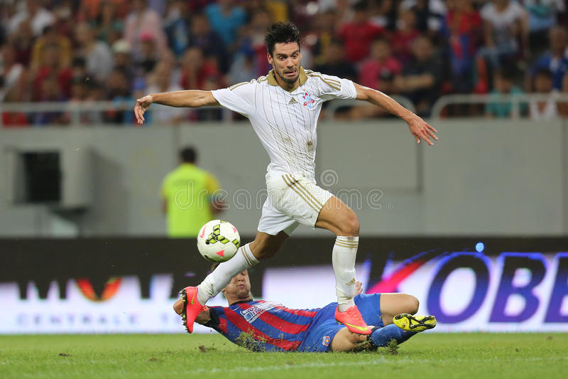 Football action - sliding tackle. Cornel Rapa takles Anderson Mineiro during the qualification match for Champions League groups between Steaua Bucharest ( royalty free stock photos