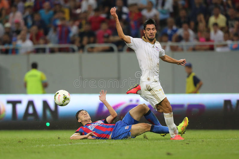 Football action - sliding tackle. Cornel Rapa takles Anderson Mineiro during the qualification match for Champions League groups between Steaua Bucharest ( stock image