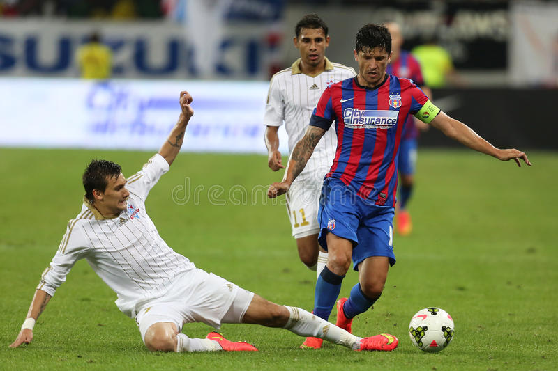 Football action - sliding tackle. Dmitri Miroshnichenko takles Cristian Tanase during the qualification match for Champions League groups between Steaua stock image