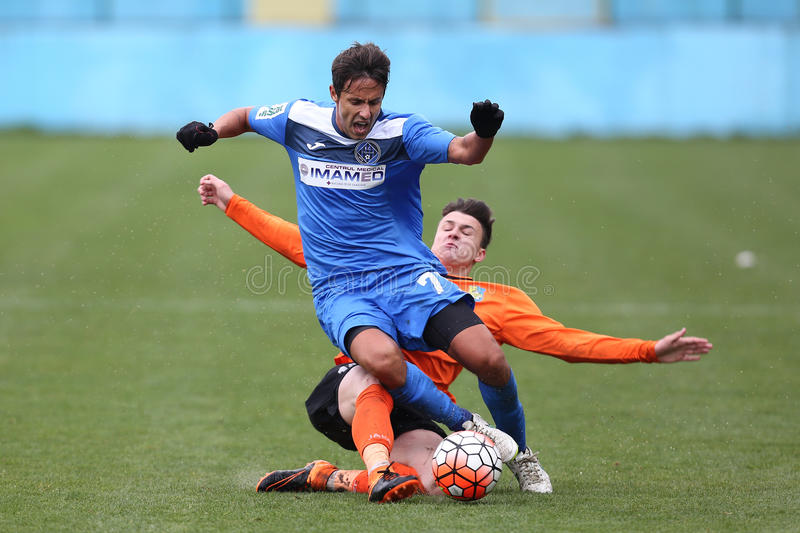 Football action - sliding tackle. Football players fighting for the ball during the game between FC Clinceni and Dunarea Calarasi, Romania Second Division stock image
