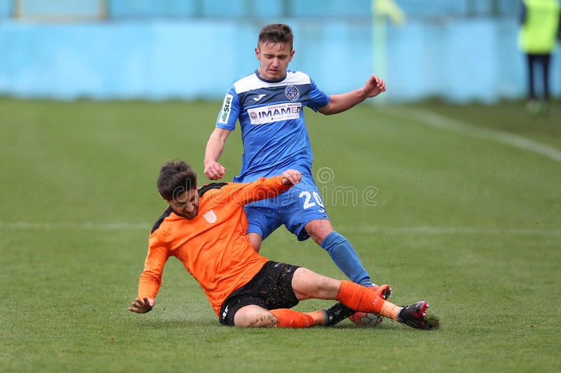 Football action - sliding tackle. Football players fighting for the ball during the game between FC Clinceni and Dunarea Calarasi, Romania Second Division royalty free stock image