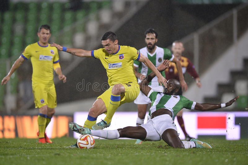 Football action - sliding tackle. Prince-Desir Gouano, player of Rio Ave Futebol Clube takles Claudiu Keseru of Steaua Bucharest in Europa League competition stock photography