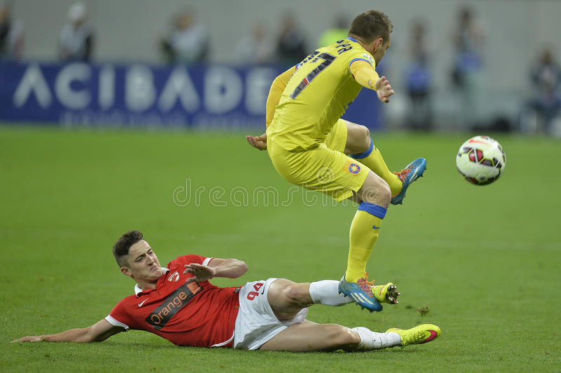 Football action - sliding tackle. Steliano Filip player of Dinamo Bucharest akles Adrian Popa of Steaua Bucharest during the Romanian football derby royalty free stock images