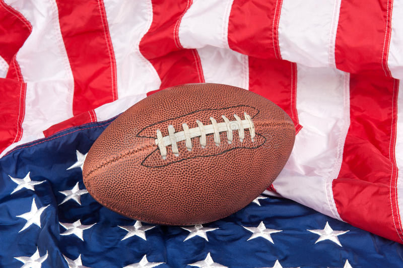 Football on American Flag. Football on an American flag shows a patriotic spirit stock images
