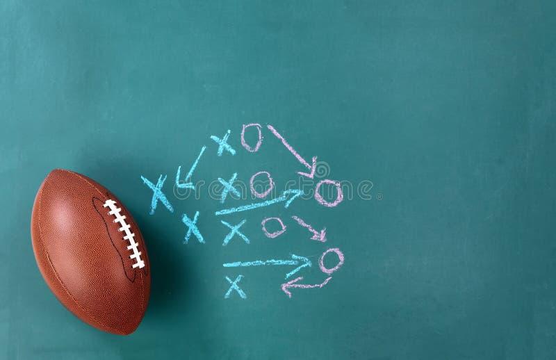 Football americano con il piano tattico sulla lavagna verde immagine stock