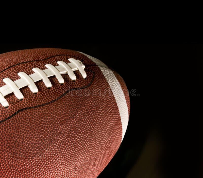 Football americano contro una priorità bassa nera fotografie stock libere da diritti