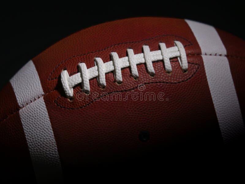 Football americano contro una priorità bassa nera fotografie stock