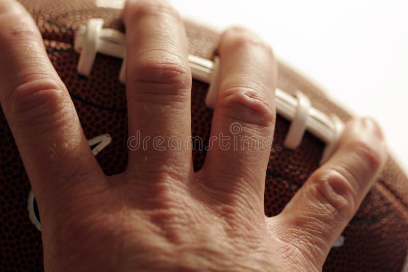 Football americano della holding della mano fotografia stock libera da diritti