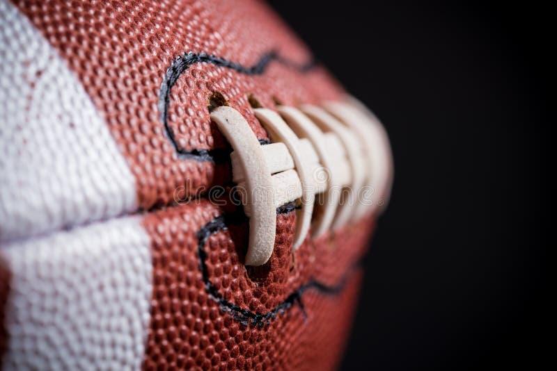 Football americano di cuoio su fondo nero immagine stock