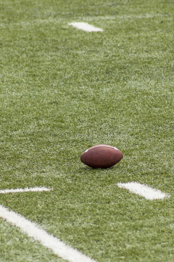 Football. A football ball in the field in the scrimmage line royalty free stock image