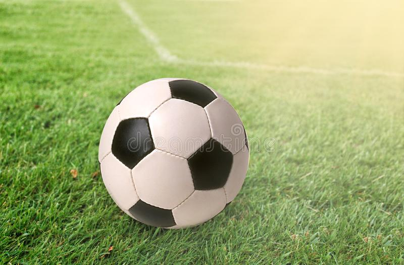 Football ball on green grass at sunny day. Football ball on green grass and all national flags royalty free stock images