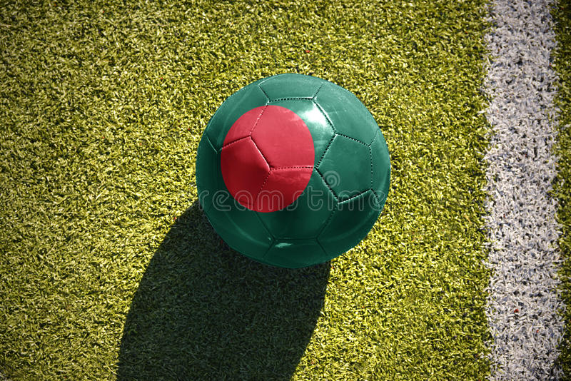Football ball with the national flag of bangladesh lies on the field stock image