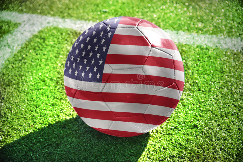 Football ball with the national flag of united states of america. Lies on the green field near the white line royalty free stock photos