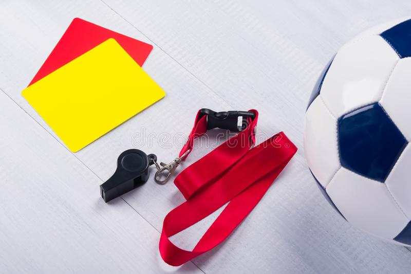 Football ball, two penalty cards and a whistle for the referee, on a gray background royalty free stock images