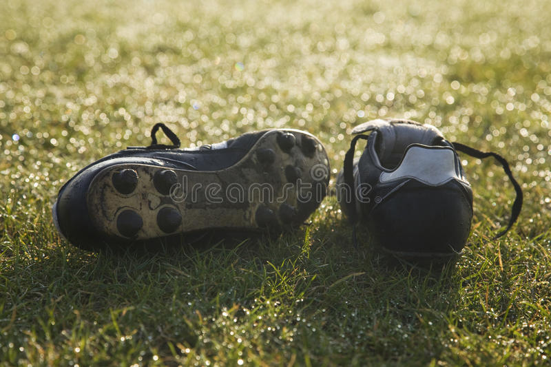 Football boots on a empty football pitch stock photos