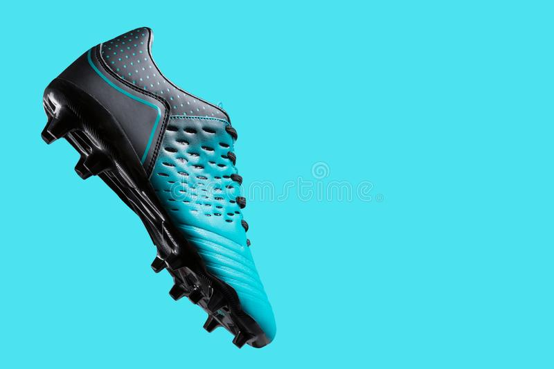 Football boots hovering in the air, as if hitting the ball, concept, sports shoes, on a turquoise background royalty free stock photos