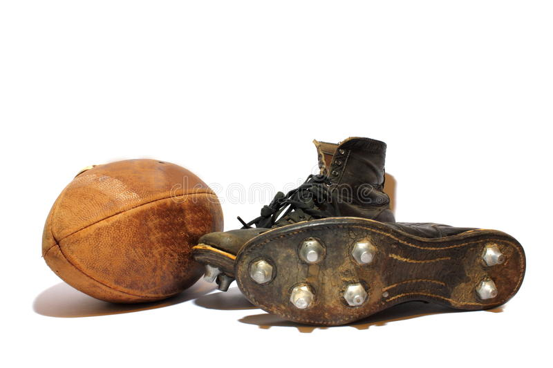 Football and Cleats. Antique football and cleats sitting on an isolated background royalty free stock images