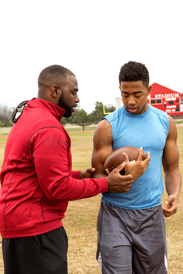 Football coach coaching an athlete. Football coach instructing a football player royalty free stock image