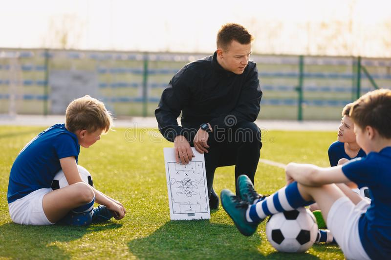 Football coach coaching children. Soccer football training session for children. Young coach teaching kids on football field. Football tactic education. Coach royalty free stock photography