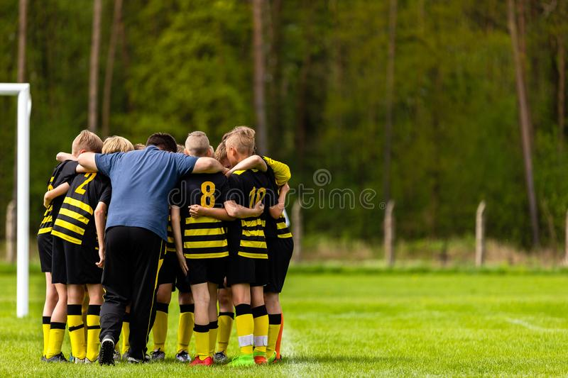 Football Coaching. Young Boys Having Pep Talk with Coach Before the Tournament Match. Kids Soccer Academy Team on the Pitch stock images