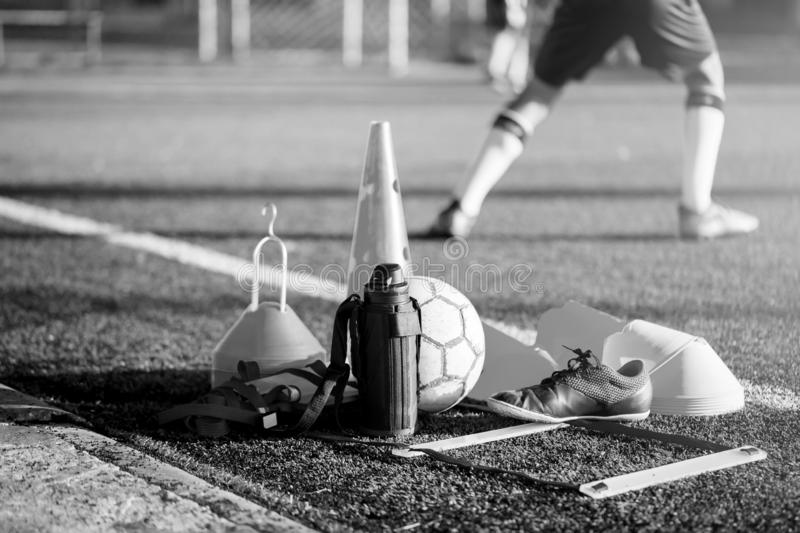 Football, cool flask, black red sports shoes and soccer training equipment. Black and white picture of Football, cool flask, black red sports shoes and soccer stock photos