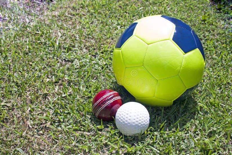 Football Cricket And Hockey Balls On Green Grassy Field royalty free stock photos