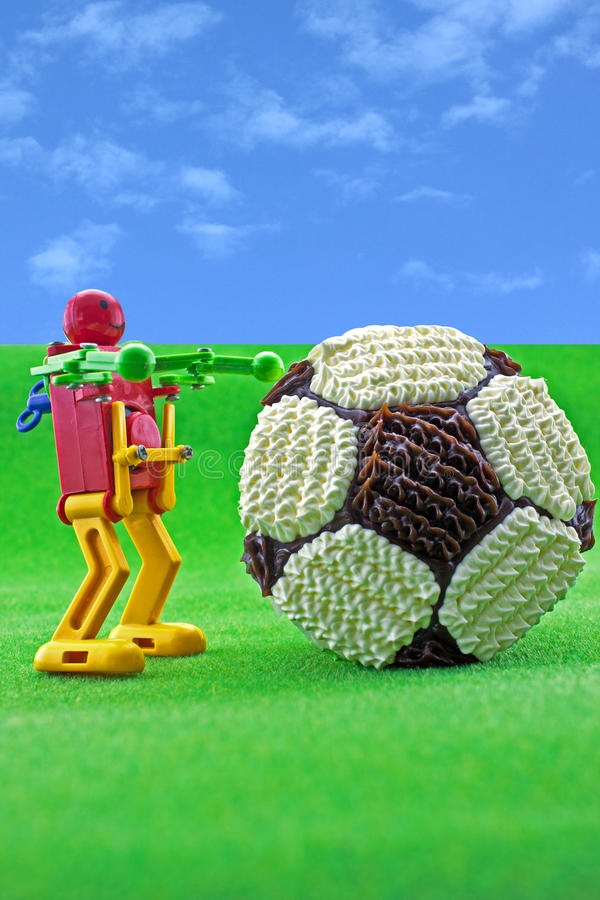 Football cupcake on green grass. Football cupcake and robot toy on green grass background stock images