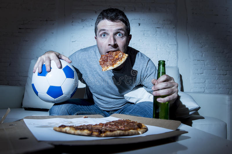 Football fan man watching soccer game on tv at home sofa couch with soccer ball and pizza in his mouth royalty free stock images