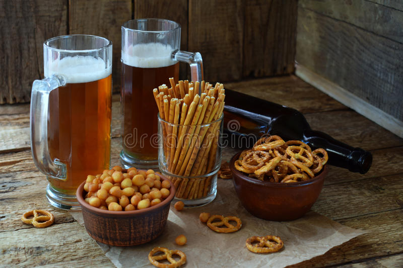 Football fan set with mugs of beer, bottle and salty snacks on wooden background. Crackers, pretzel, salted straws, nuts, dried fi. Sh. Junk food for beer or stock photography