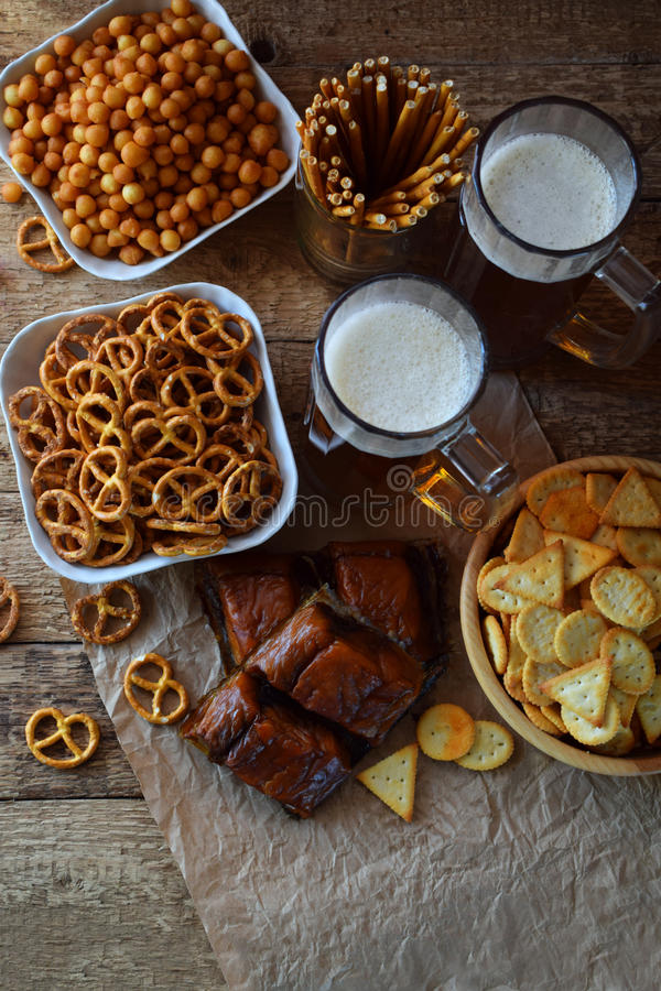 Football fan set with mugs of beer and salty snacks on wooden background. Crackers, pretzel, salted straws, nuts, dried fish. Junk. Food for beer or cola royalty free stock images