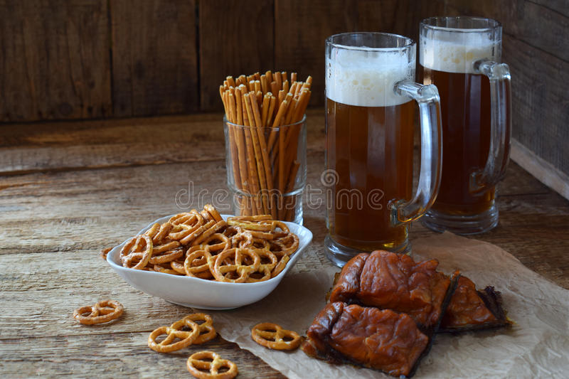 Football fan set with mugs of beer and salty snacks on wooden background. Crackers, pretzel, salted straws, nuts, dried fish. Junk. Food for beer or cola stock images