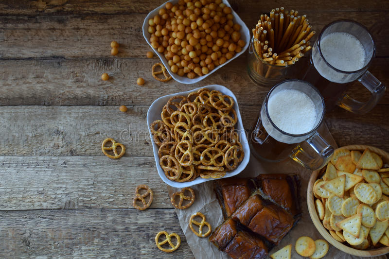 Football fan set with mugs of beer and salty snacks on wooden background. Crackers, pretzel, salted straws, nuts, dried fish. Junk. Food for beer or cola stock photos