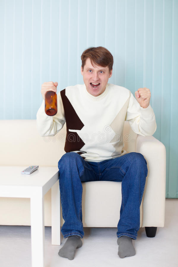 Download Football Fan Sitting On Sofa With TV And Beer Royalty Free Stock Images - Image: 12817349